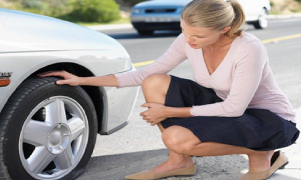 Woman using crouching by car with flat tire